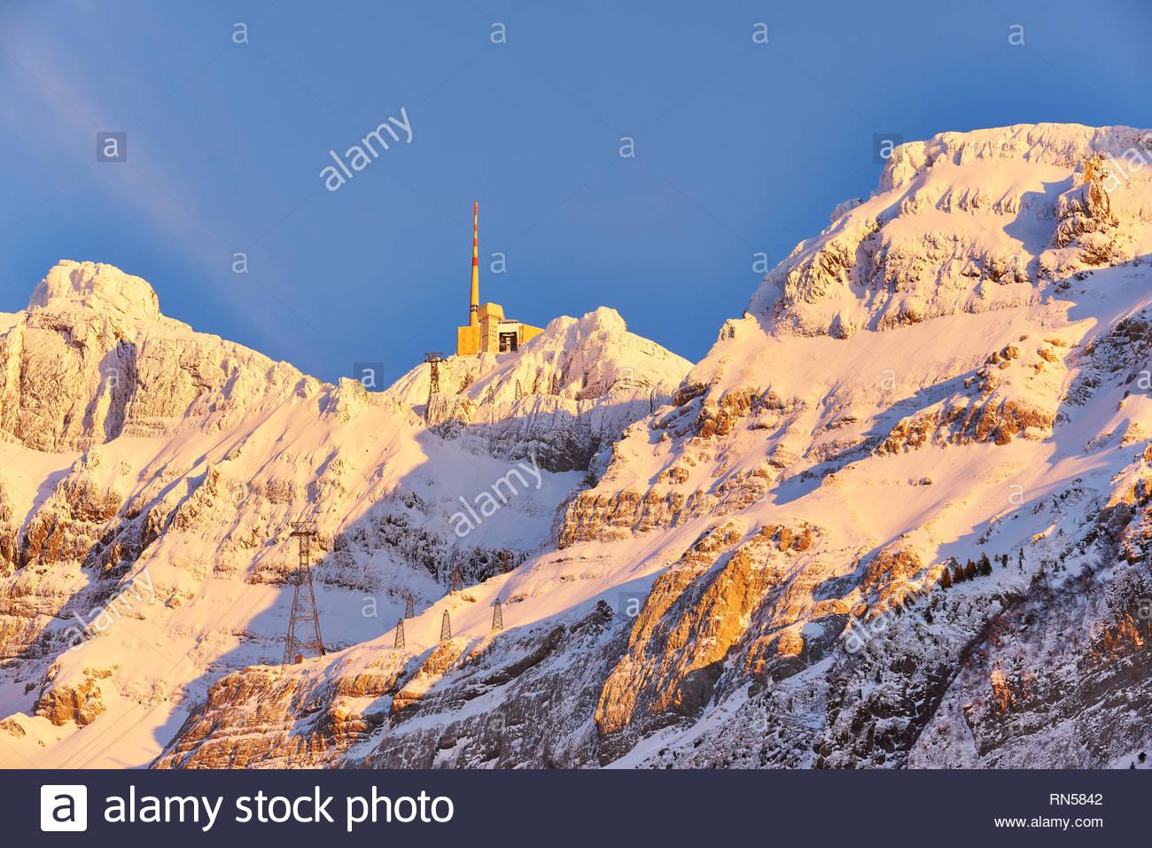 Säntis im Winter, Bergstation mit Sendemast, schneebedecktes Felsmassiv im gelben Abendlicht, blauer Himmel, Seilbahnmasten - Stock Image