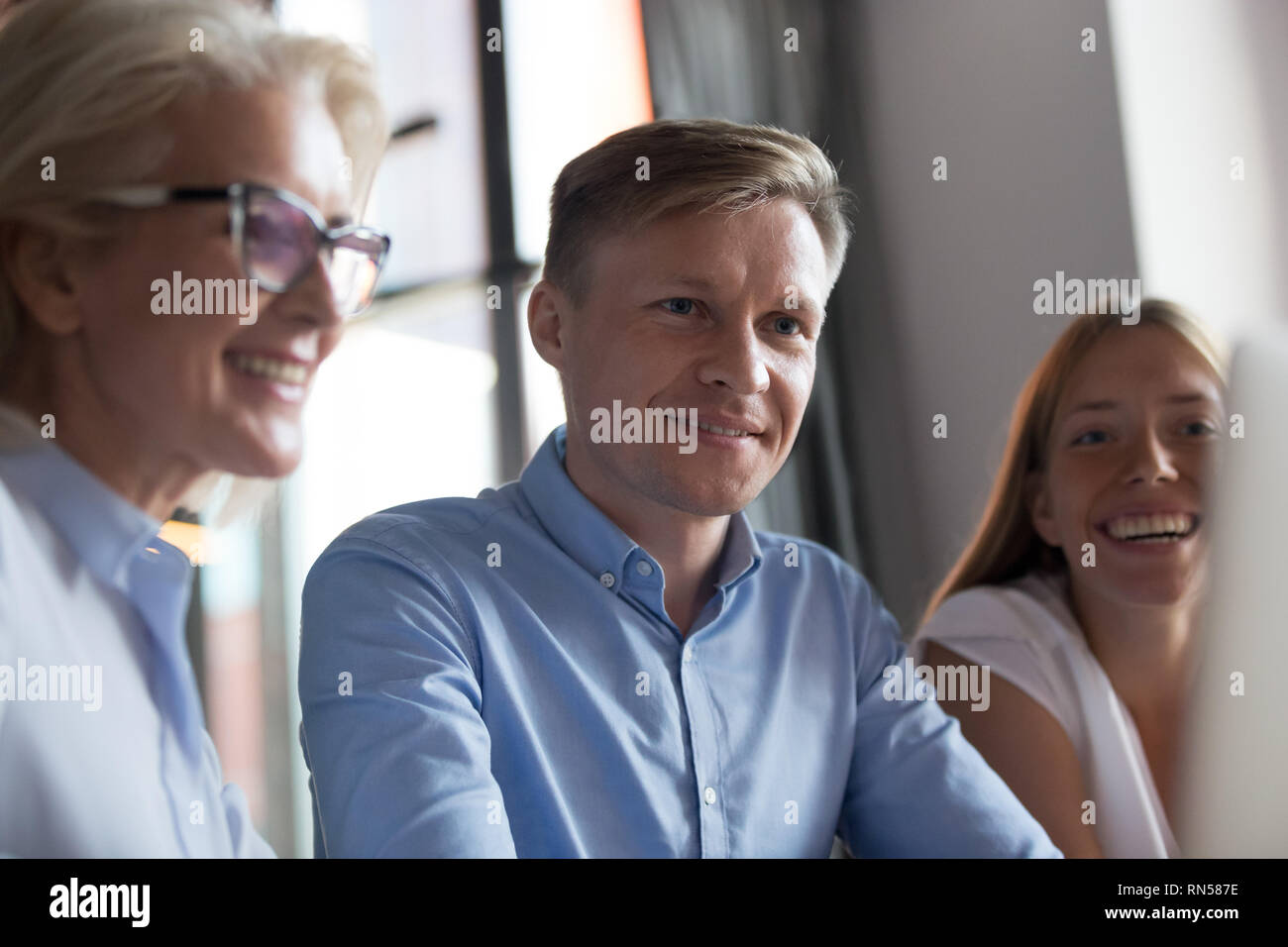 Confident caucasian boss discussing with employees during briefing - Stock Image