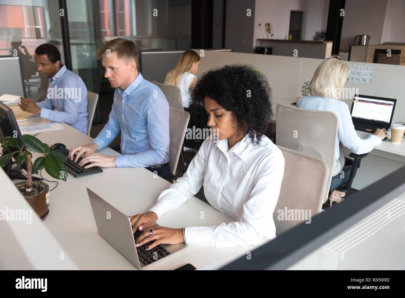 Diverse millennial employees sitting at desk working in coworking space - Stock Image