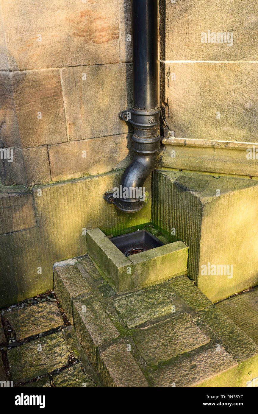 Cast iron rainwater pipe outlet on grade 1 listed chuech mounted on stone wall - Stock Image