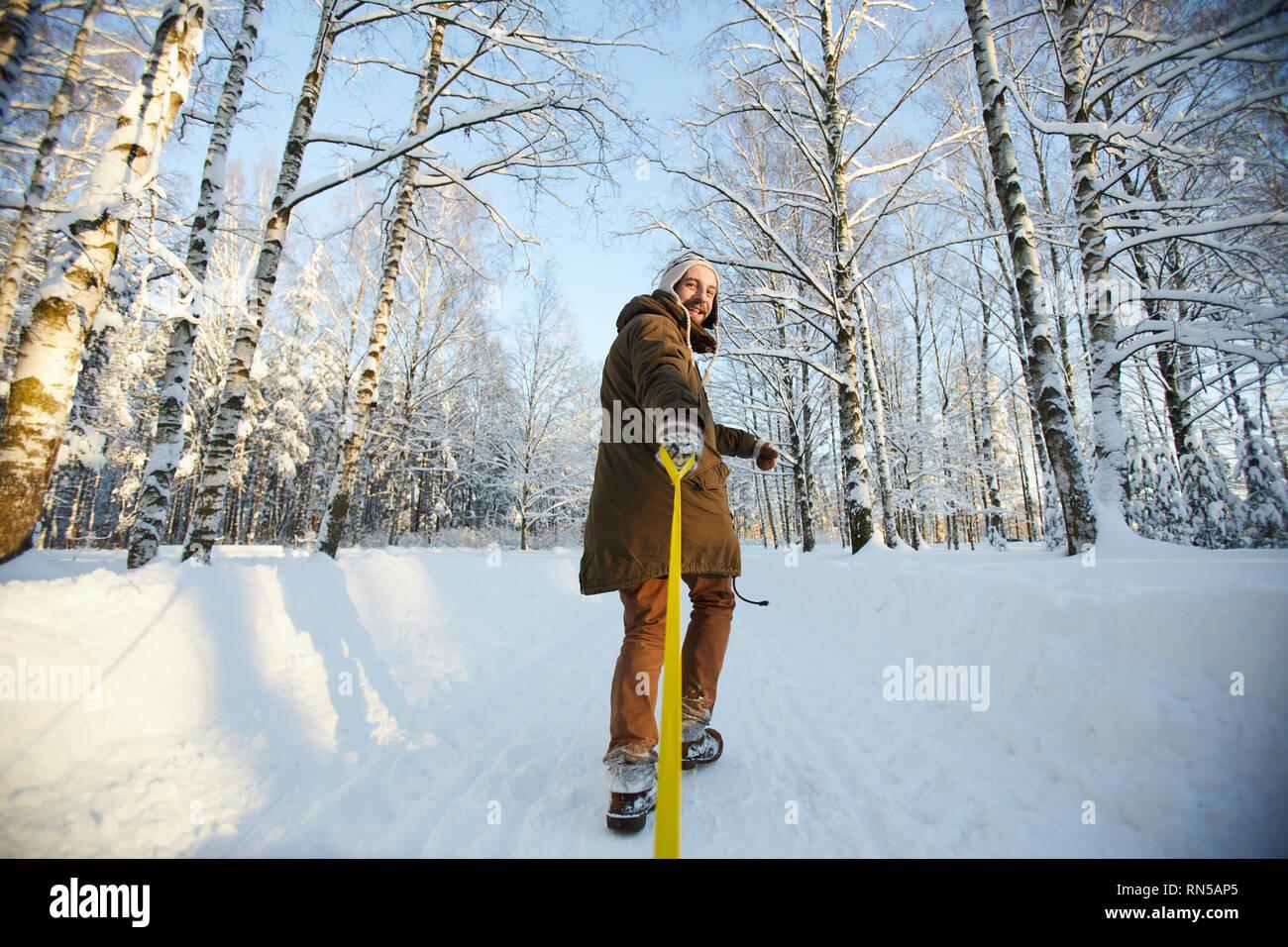 Happy Man Tugging Sleigh - Stock Image