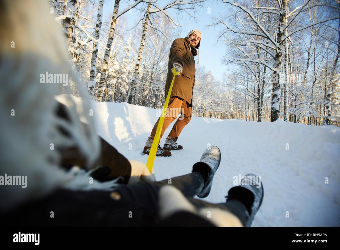 Mature Man Tugging Sleigh - Stock Image