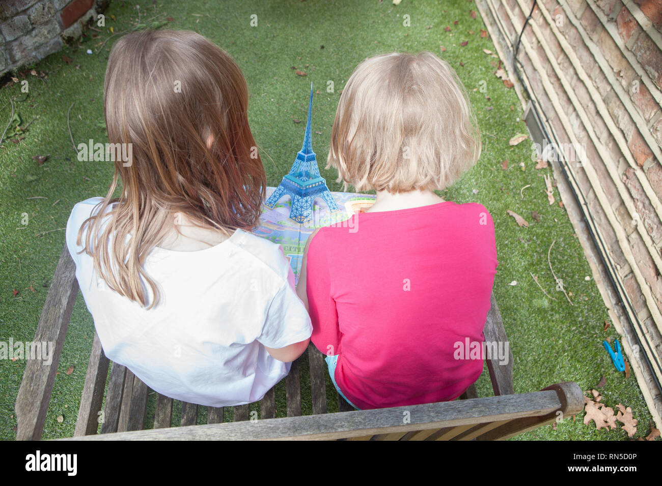 two young girls reading a pop up book on Paris in their garden Stock Photo