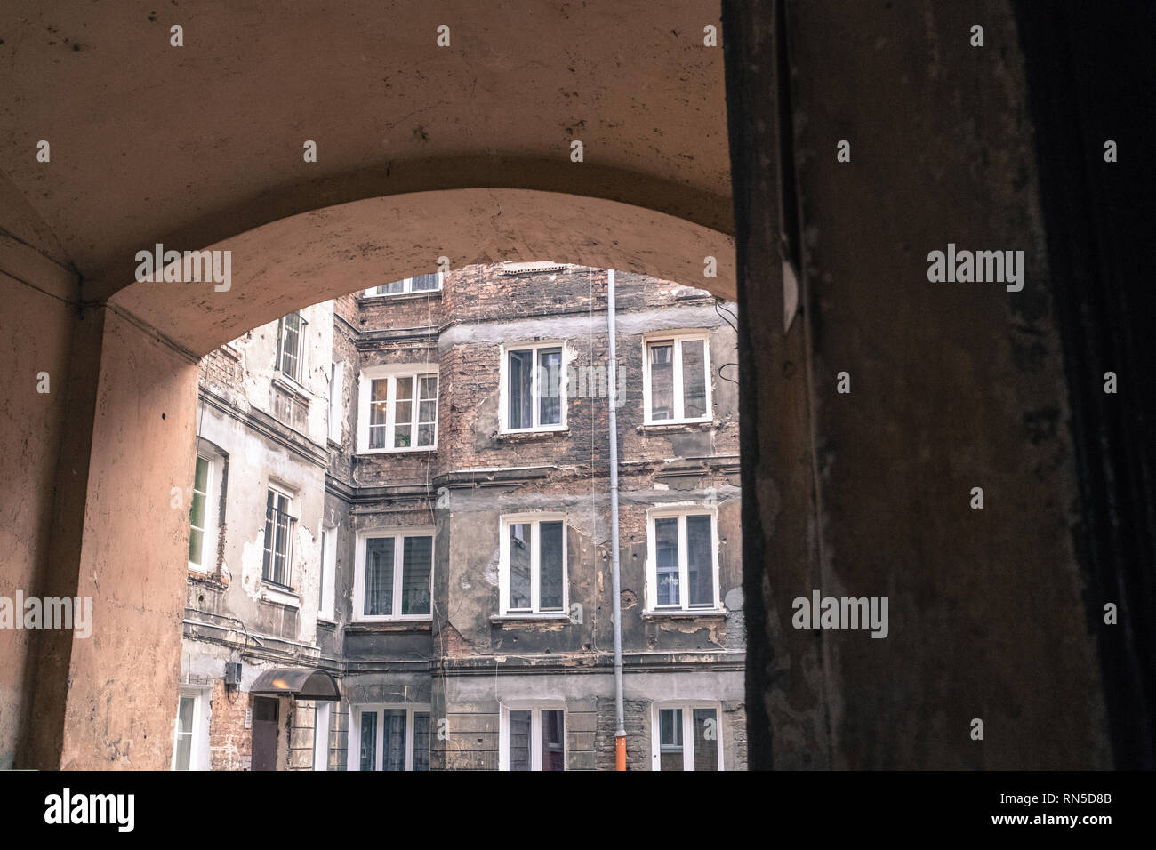 Tenement House in Warsaw seen through an archway into the courtyard Stock Photo
