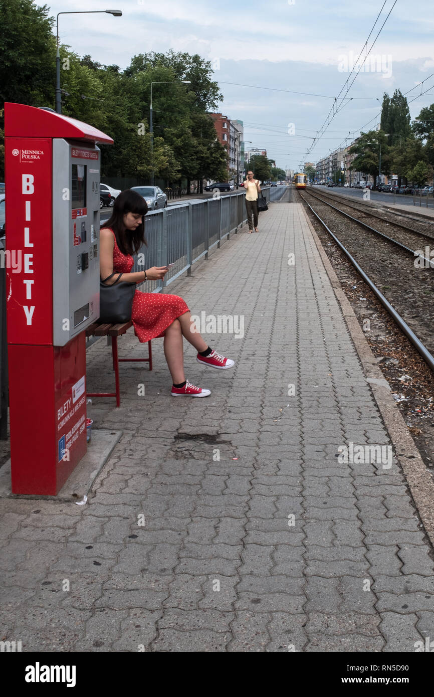 Woman in a red dress with red shoes sitting on a train platform next to a red ticket machine Stock Photo