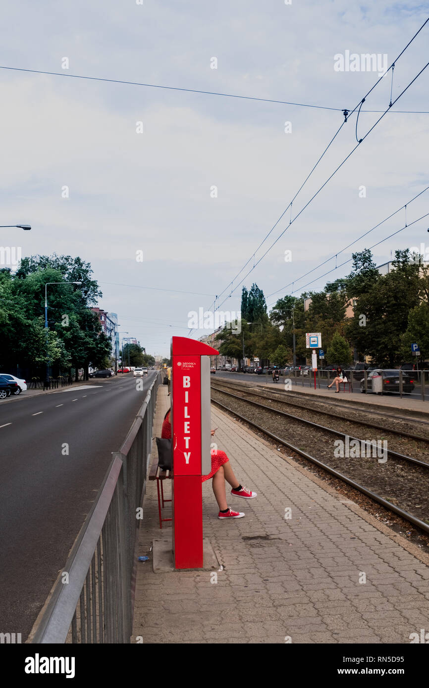 Woman in a red dress with red shoes sitting on a train platform hidden behind a red ticket machine Stock Photo