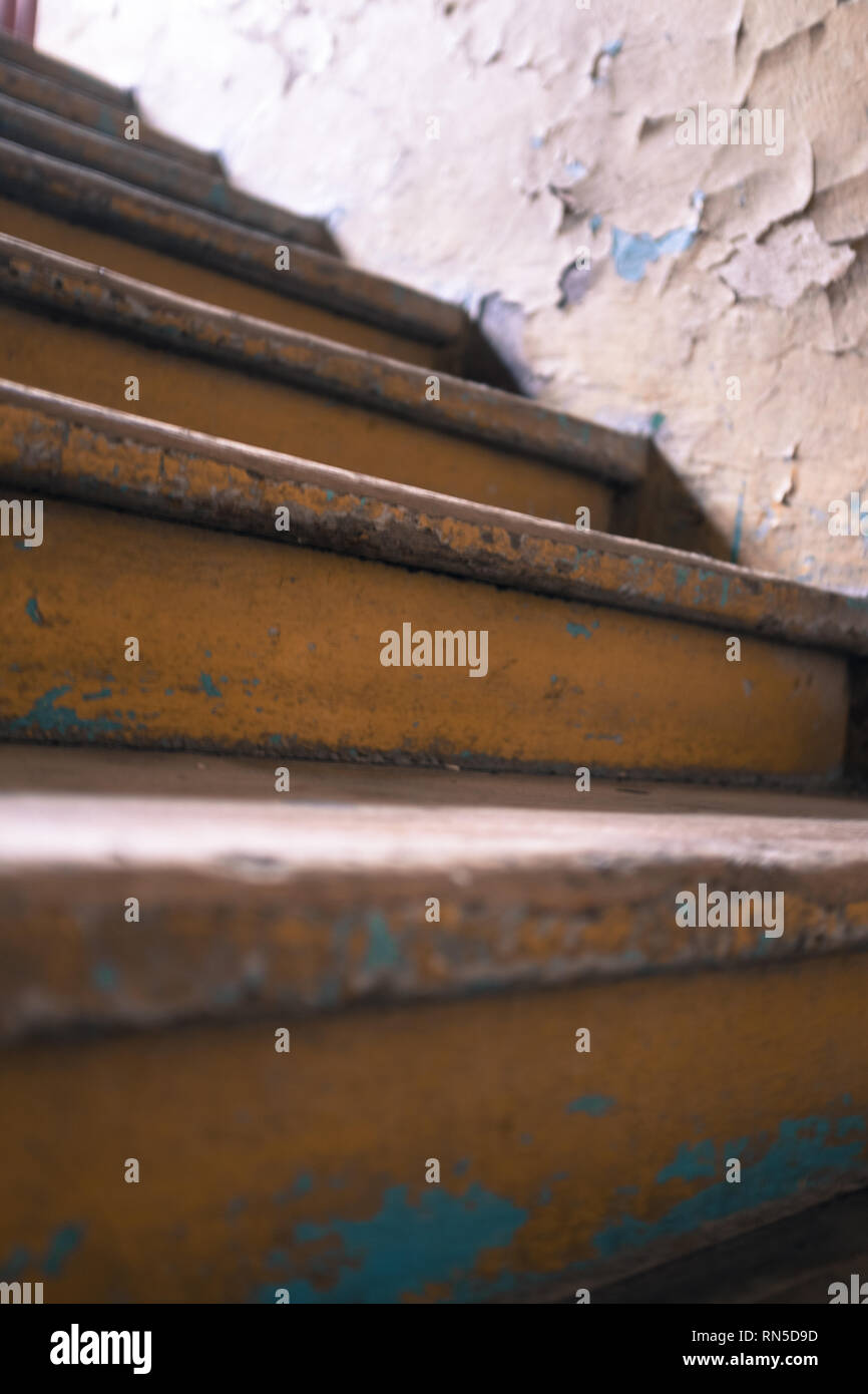 stairs leading up towards a light with crumbling wall and old paint Stock Photo