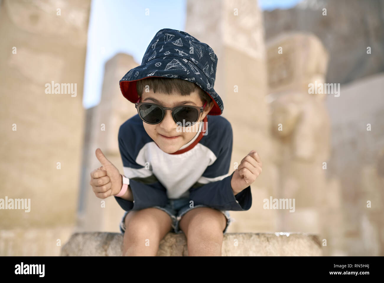 Grimacing small boy in sunglasses sits on the stone on the blurred sunny background of the ancient ruins in Luxor in Egypt. He wears a blue-red hat wi - Stock Image