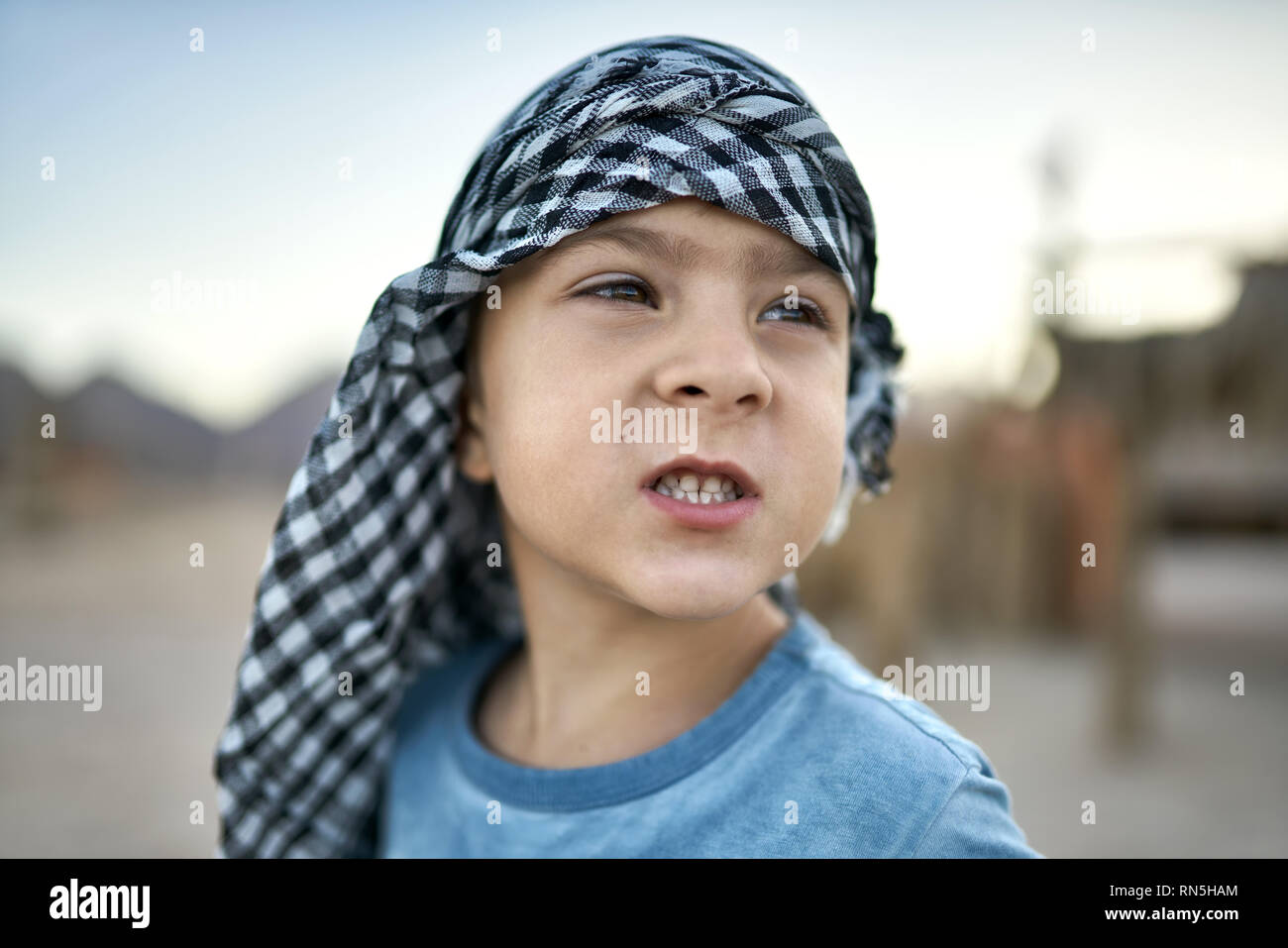 Small boy in checkered keffiyeh grimacing outdoors - Stock Image