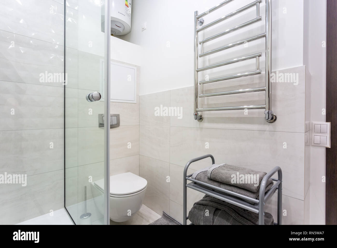 toilet and detail of a corner shower cabin with wall mount shower attachment - Stock Image