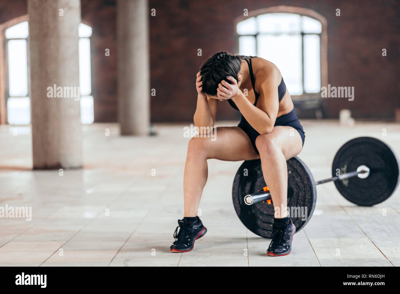 tired athlete holding her head during the break. full length photo. copy space. problem, dissatisfaction - Stock Image