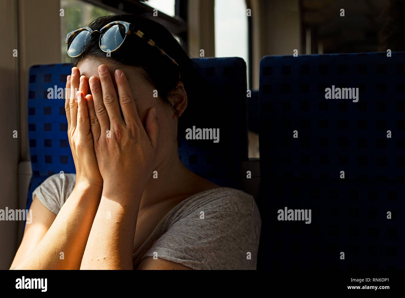 A lone white female hides her face with her hands on a train. - Stock Image