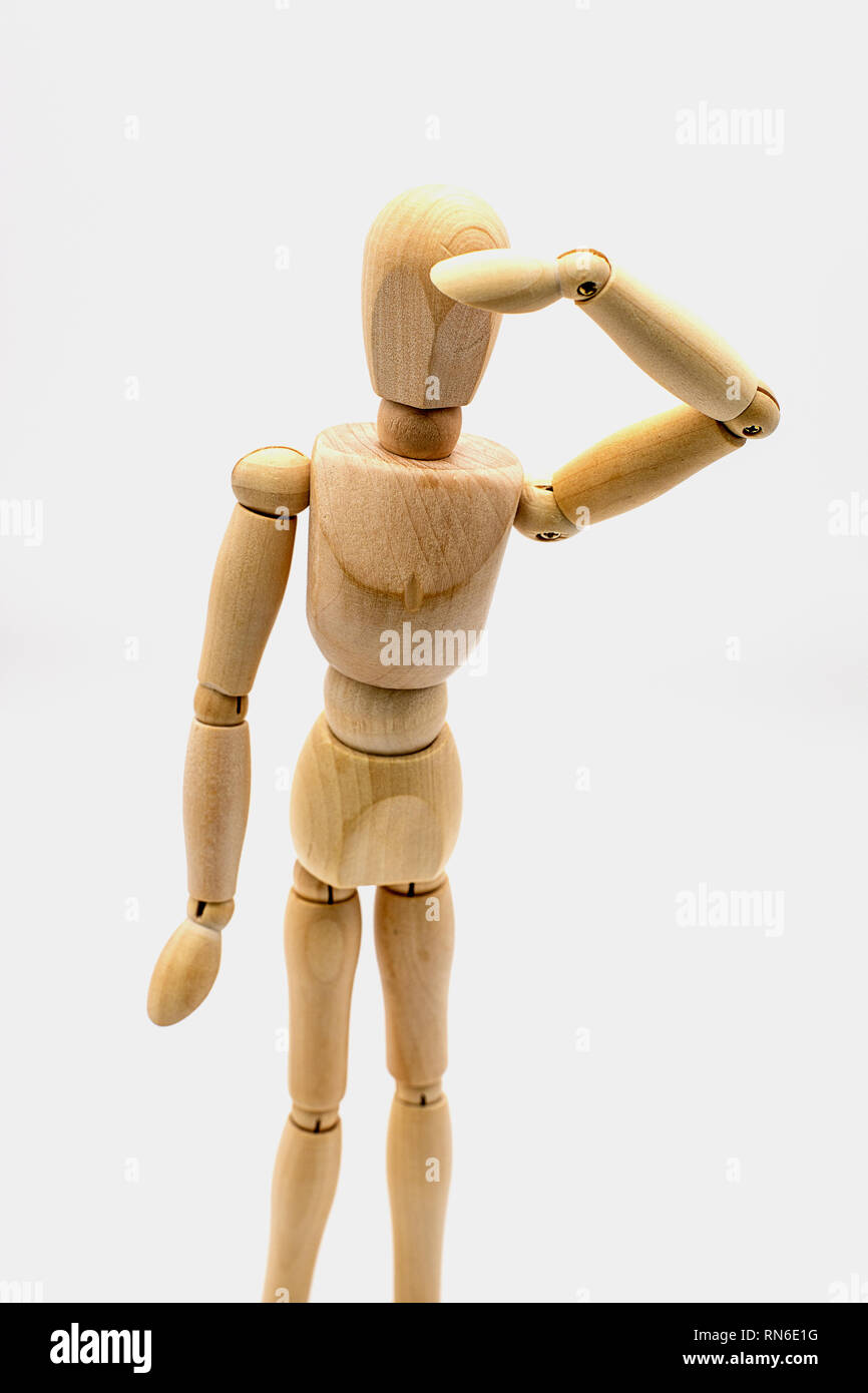 wooden dummy puppet keeping an eye out - Stock Image