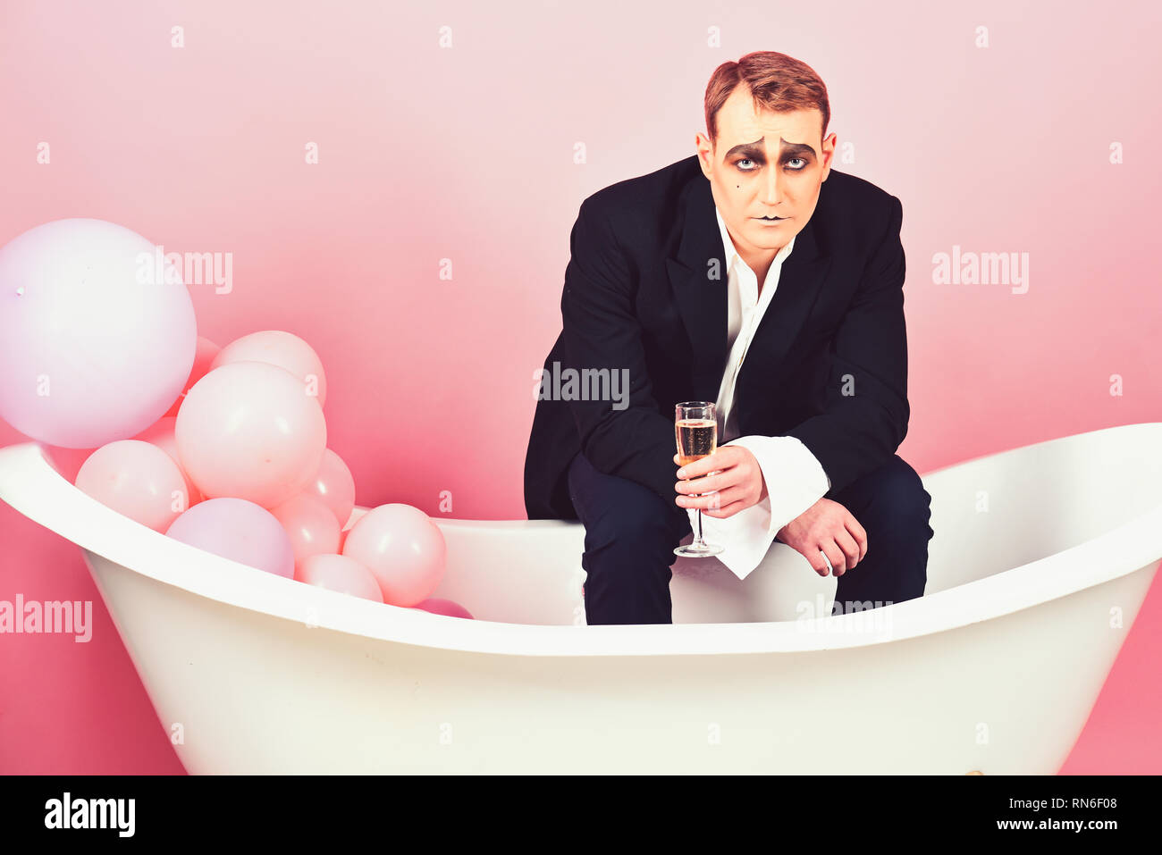 The drink of the moment. Mime man celebrate with champagne in bath. Comedian actor enjoy theatre party celebrating. Mime actor has celebration party - Stock Image
