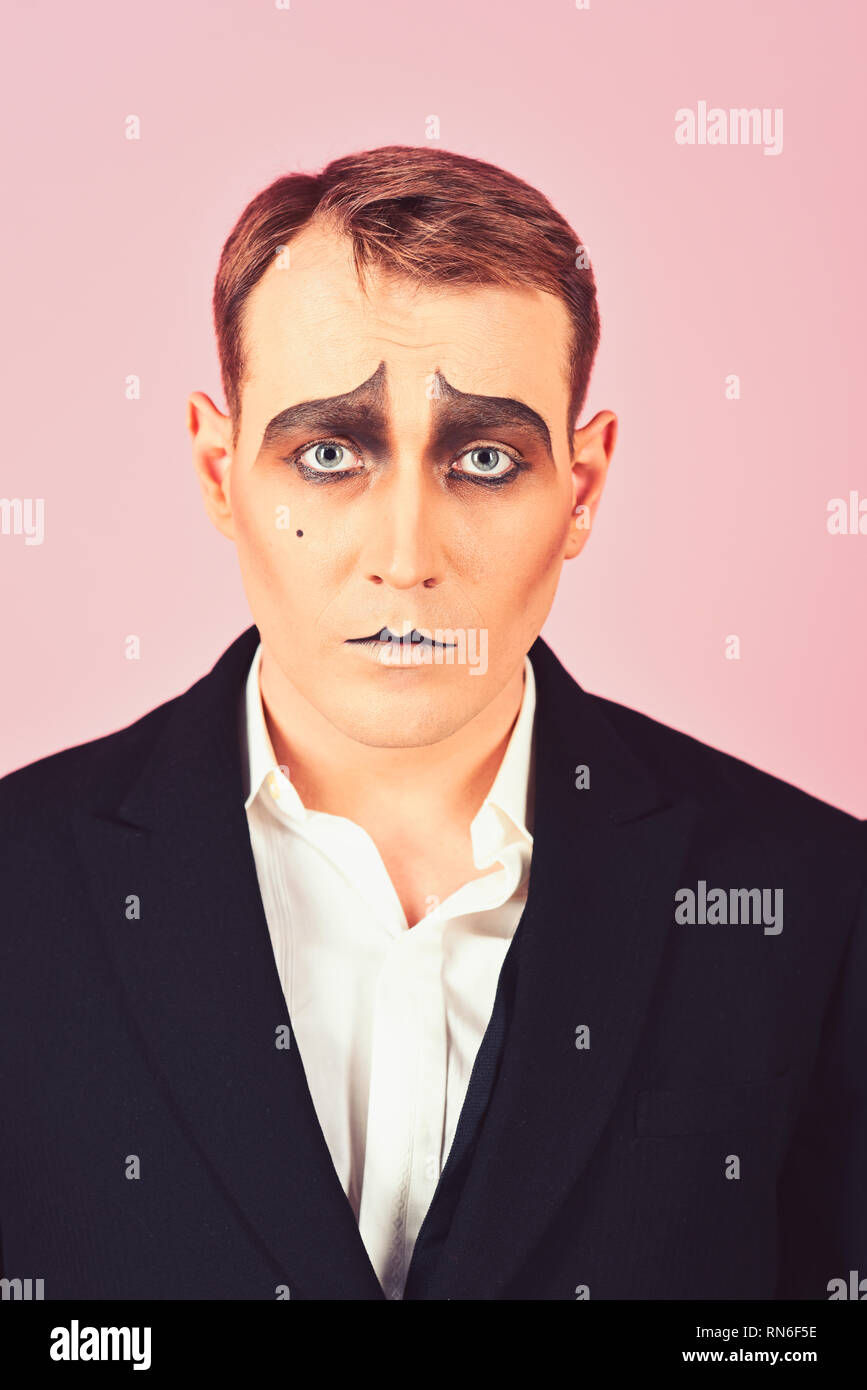 He is much of an actor. Mime with face paint. Mime artist. Man with mime makeup. Theatre actor miming. Stage actor miming. Theatrical performance art - Stock Image