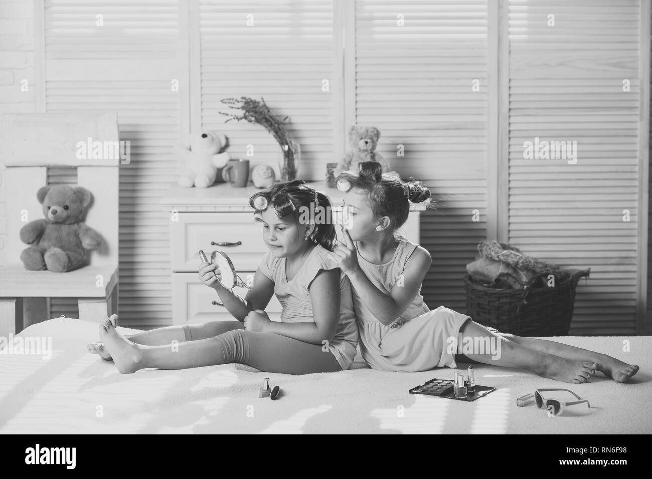 Children smile and sit on bed with lipstick and mirror - Stock Image
