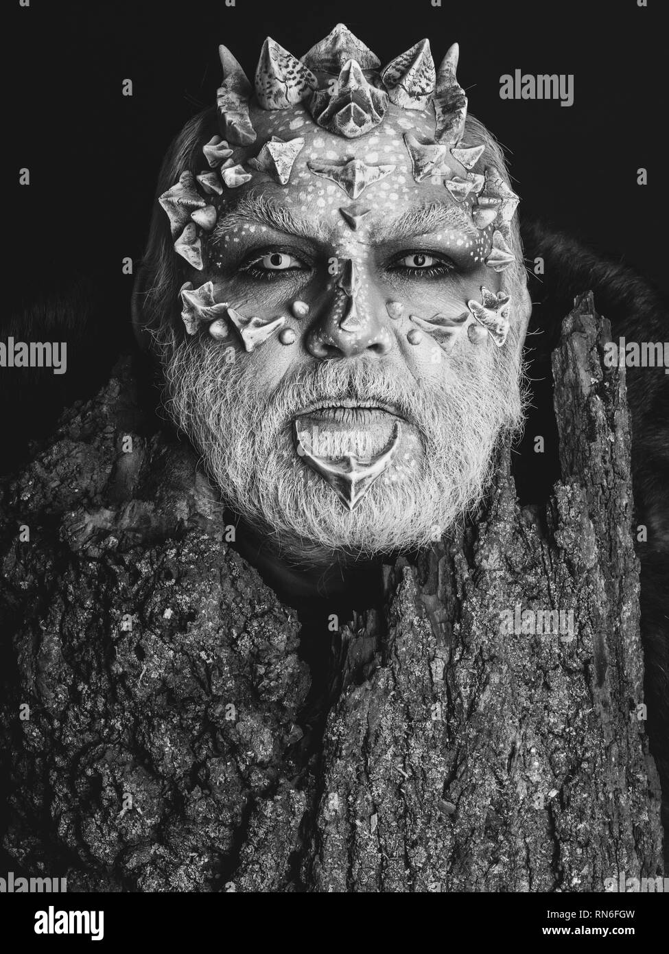 Man with dragon skin and bearded face - Stock Image