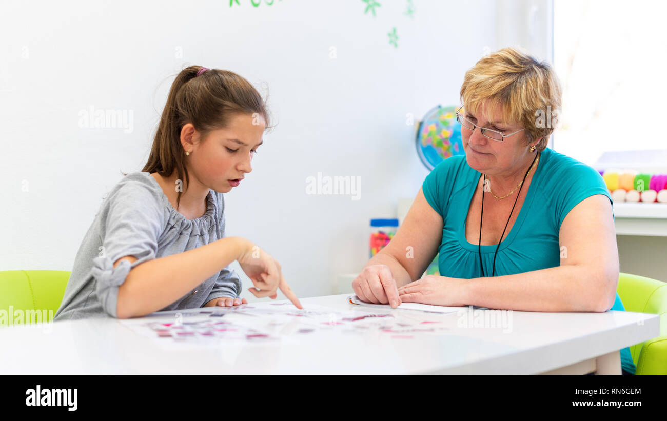 Mature female therapist working with a teenage girl with learning difficulties to master logical tests. - Stock Image