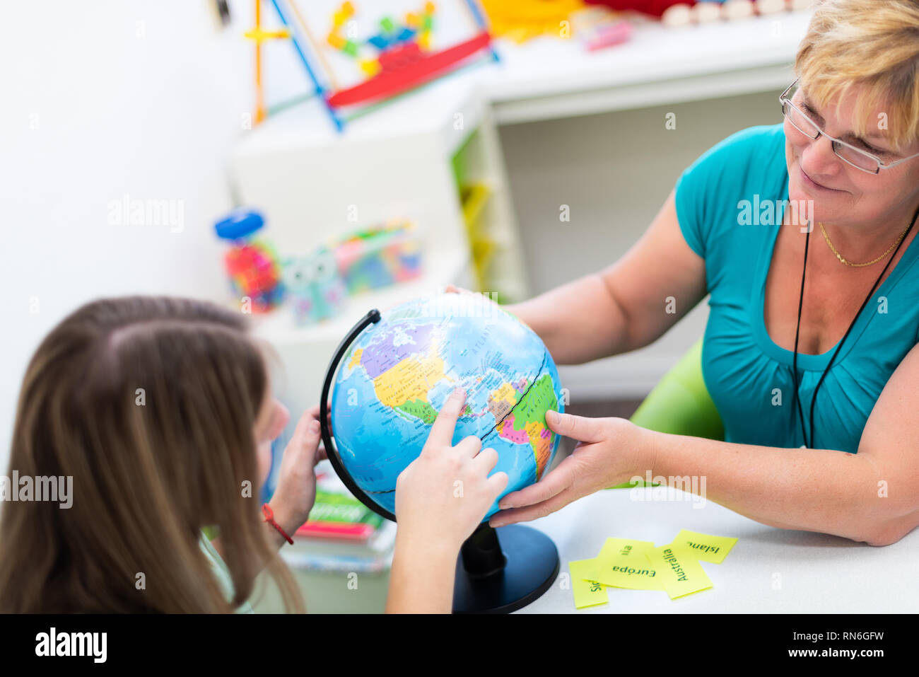Mature female therapist working with a teenage girl with learning difficulties. Private geography tutoring session. Teacher with teenage student in cl - Stock Image