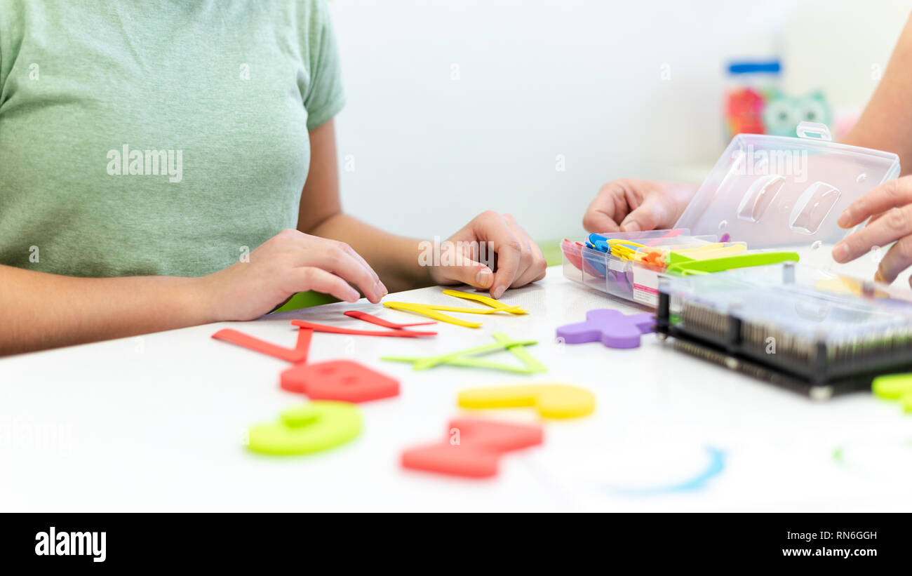 Therapist helping teenage girl with learning difficulties during child therapy. Top view hand detail of a therapist with patient. - Stock Image