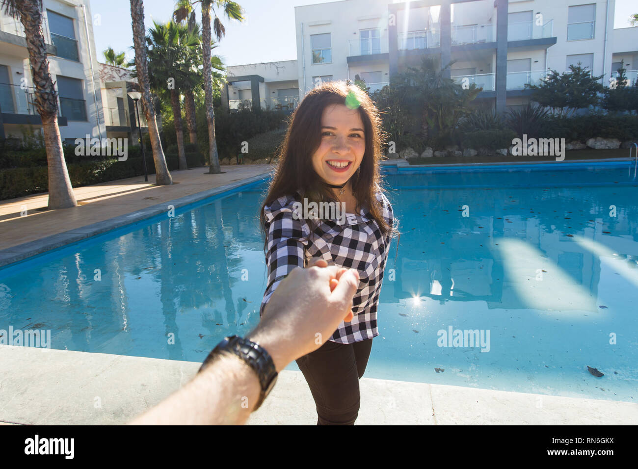 Follow Me Vacation Concept Happy Young Woman Holding Boyfriend S Hand At Resort Near Swimming Pool Stock Photo Alamy