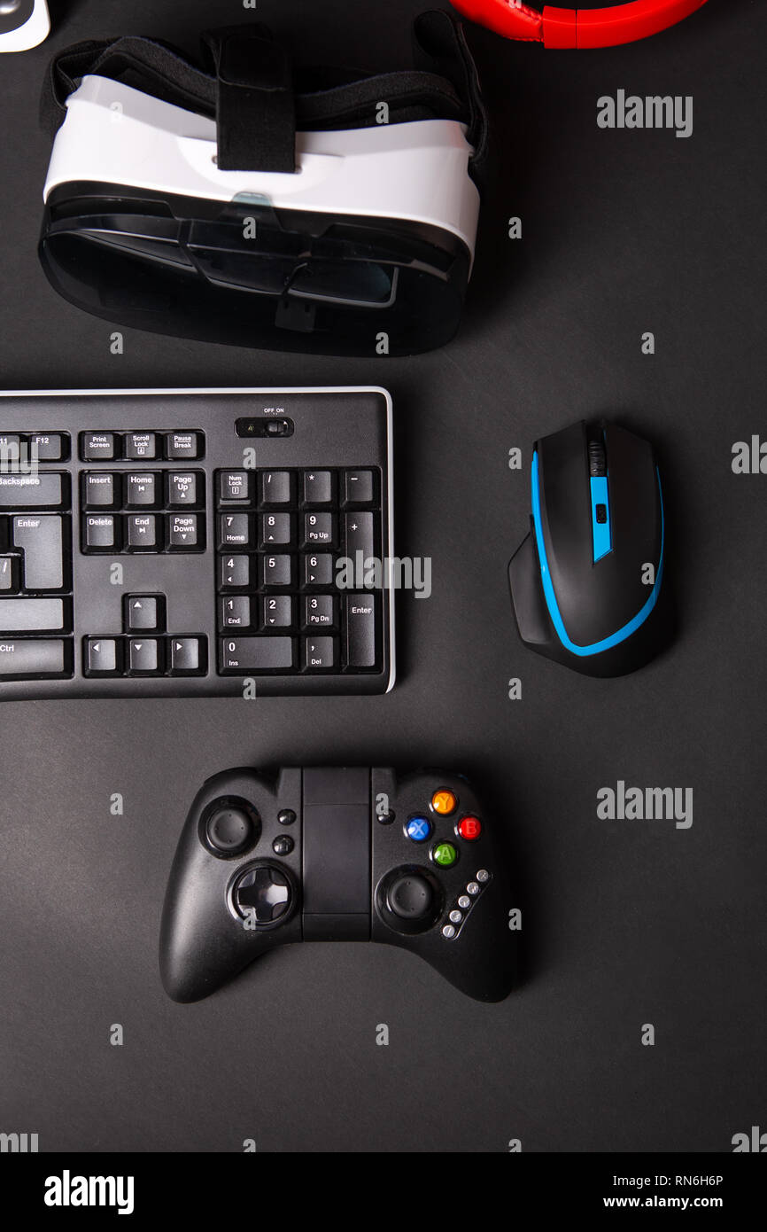 Top view a gaming gear, mouse, keyboard, joystick, headset, VR Headset on black table background. - Stock Image