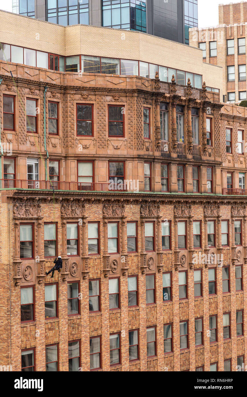 Industrial engineer rappelling down the side of a building on a structural inspection, New York City, USA - Stock Image