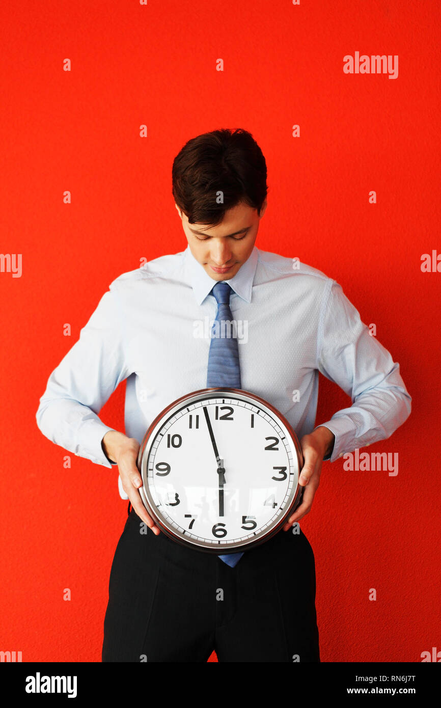 Business man holding wall clock on red background. Race against time, time goes by, running out of time, no time for work, time running, time is money - Stock Image