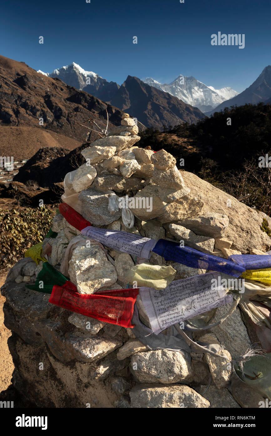 Nepal, Everest Base Camp Trek, Khumjung, Buddhist prayer flags tied to rough cairn of stones on mountain path - Stock Image