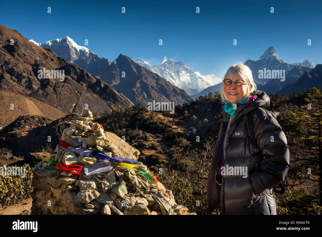 Nepal, Everest Base Camp Trek, Khumjung, senior female tourist at prayer flags tied to rough cairn of stones on mountain path - Stock Image
