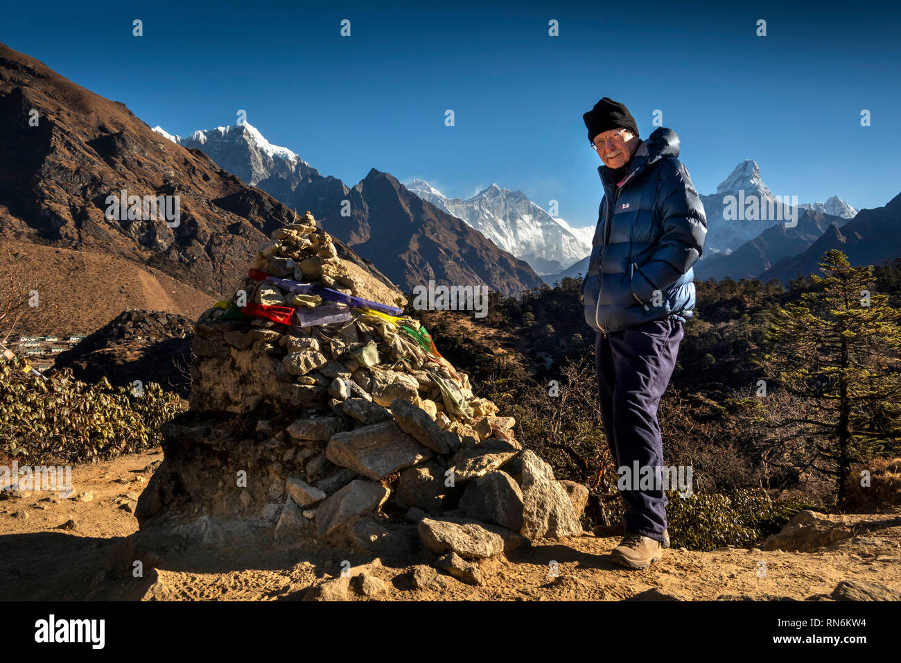 Nepal, Everest Base Camp Trek, Khumjung, senior male tourist at prayer flags tied to rough cairn of stones on mountain path - Stock Image