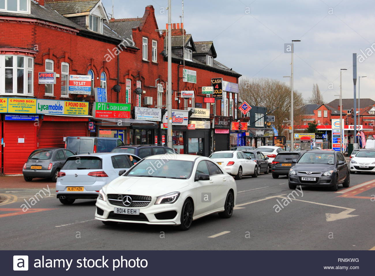 Cars in motion along Cheetham Hill Road Manchester UK with shops in background. - Stock Image