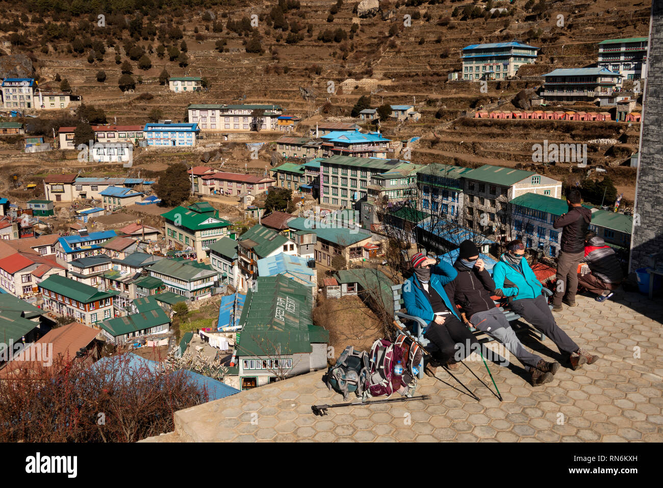 Nepal, Namche Bazaar, walkers wearing cold weather clothing resting on seat in sunshine with elevated view of town - Stock Image