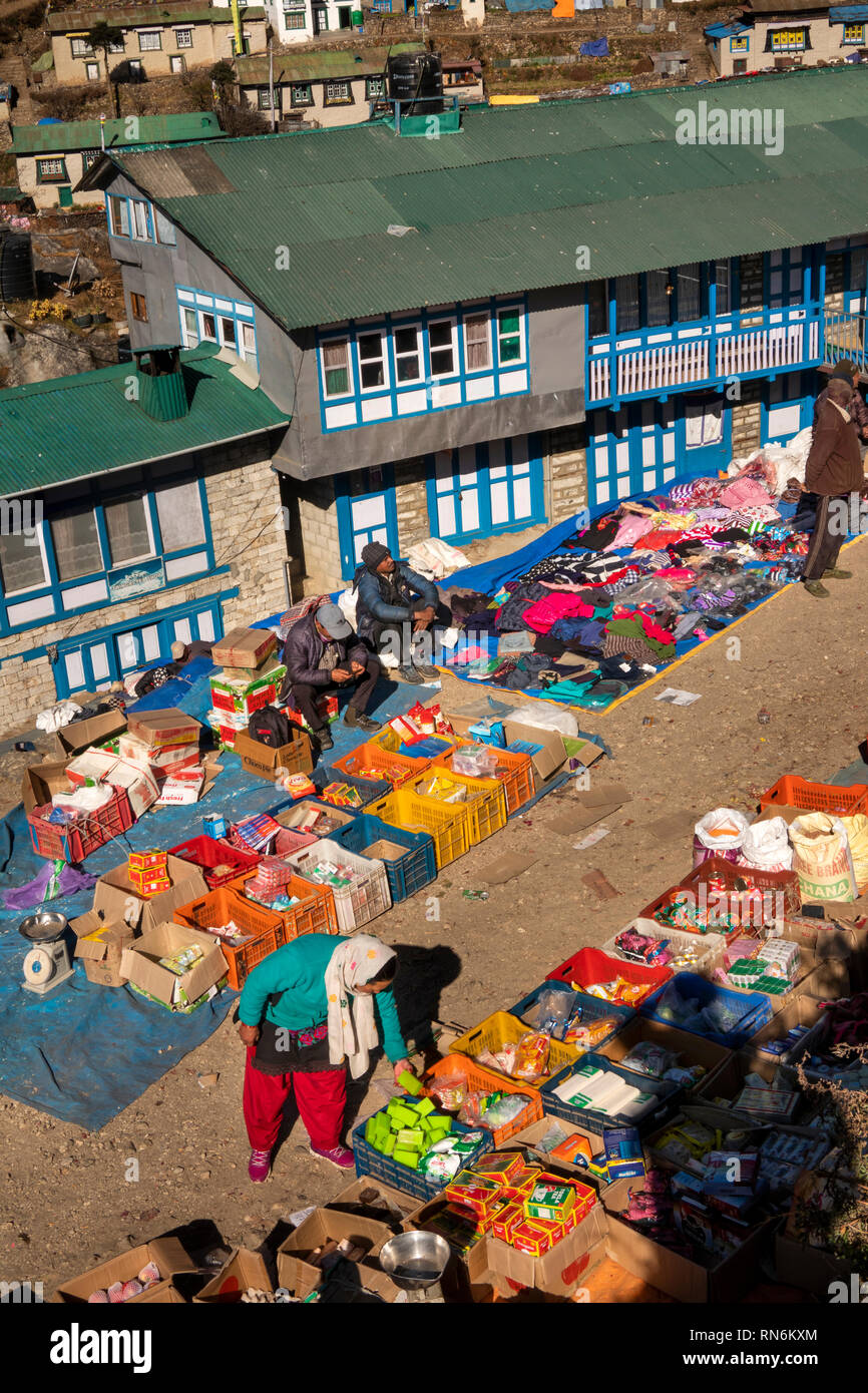 Nepal, Namche Bazaar, Market, elevated view of shopper looking at household goods displayed by trader in boxes - Stock Image