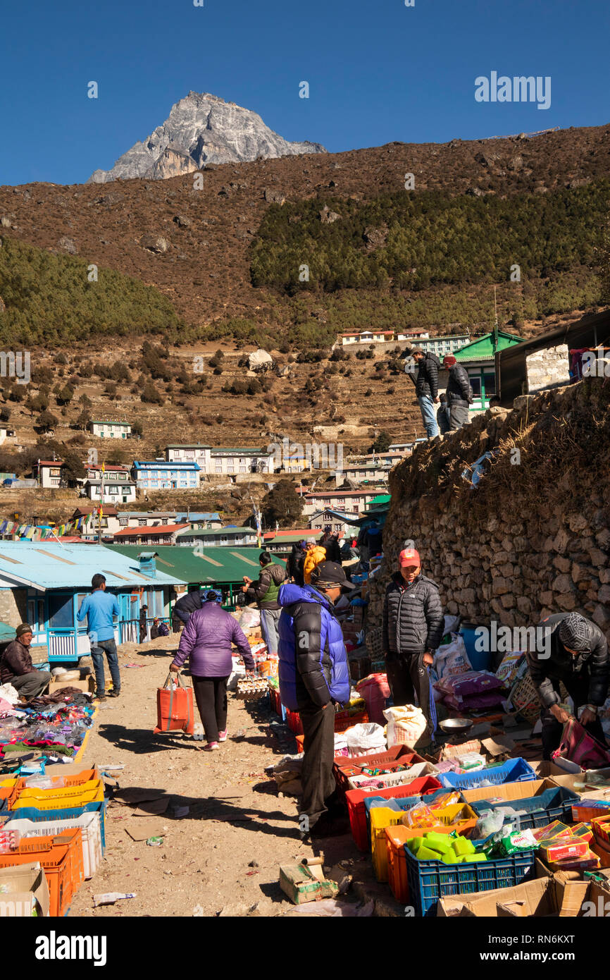 Nepal, Namche Bazaar, Market, local shoppers looking at household goods displayed by trader in boxes Stock Photo