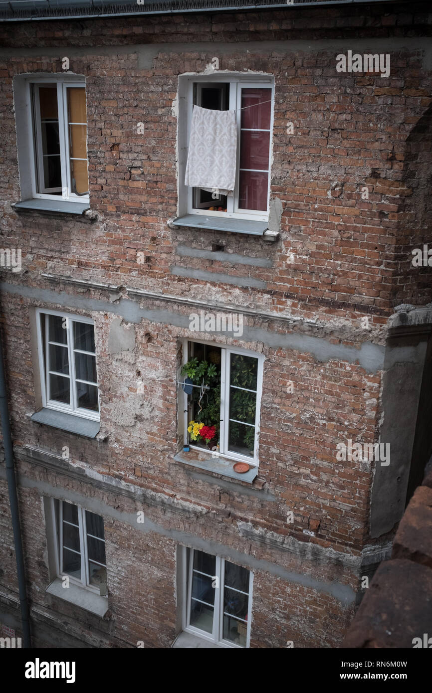 brick tenement house with washing and flowers in the windows Stock Photo