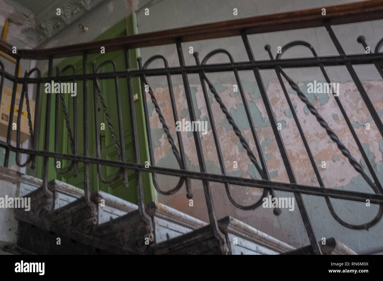 Period staircase for an apartment block leading to a green door Stock Photo
