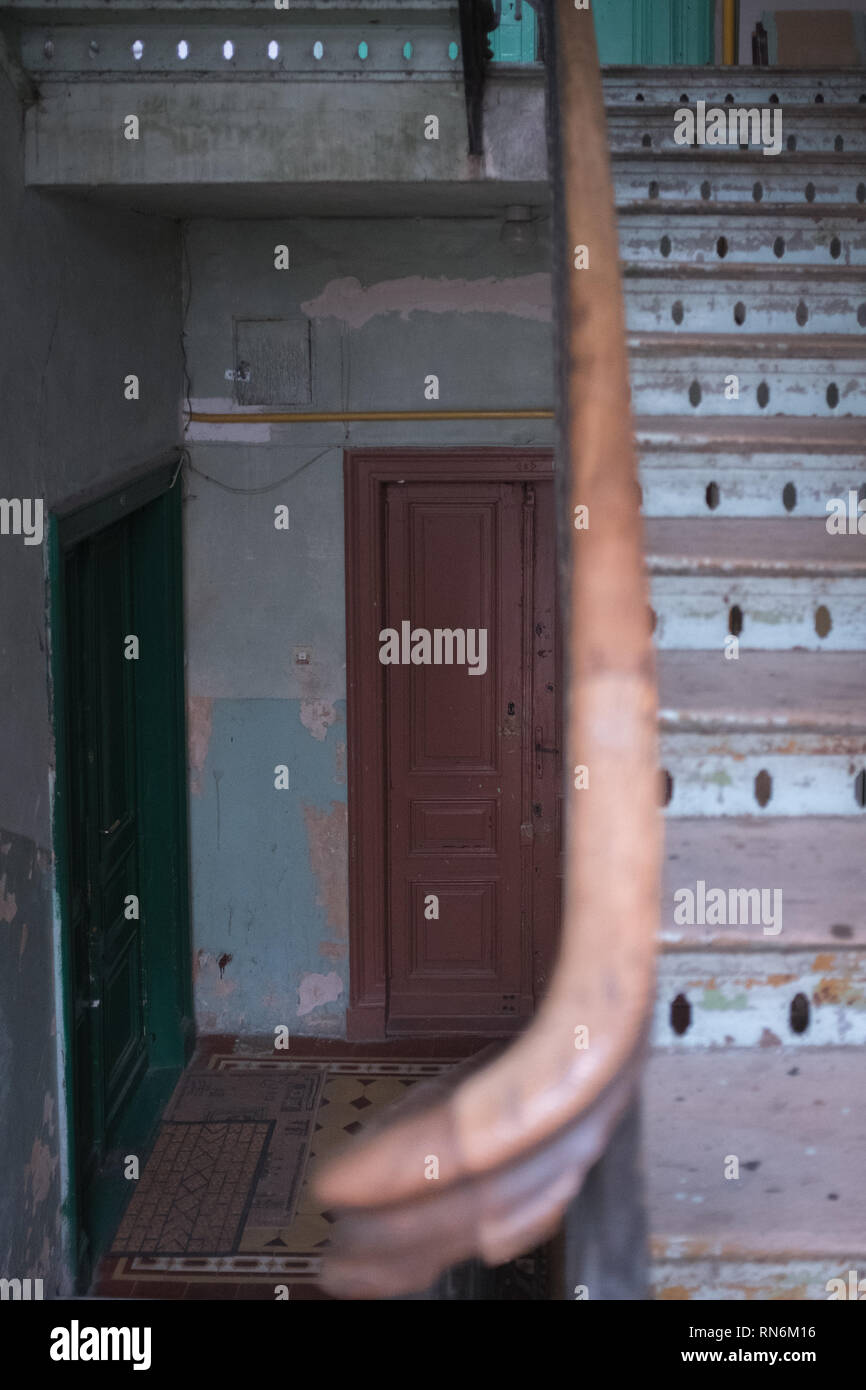 two front doors in a run down tenement house with a a wooden staircase leading to other floors Stock Photo