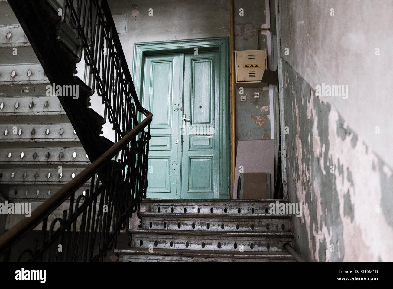 Period staircase for an apartment block leading to a green door - Stock Image