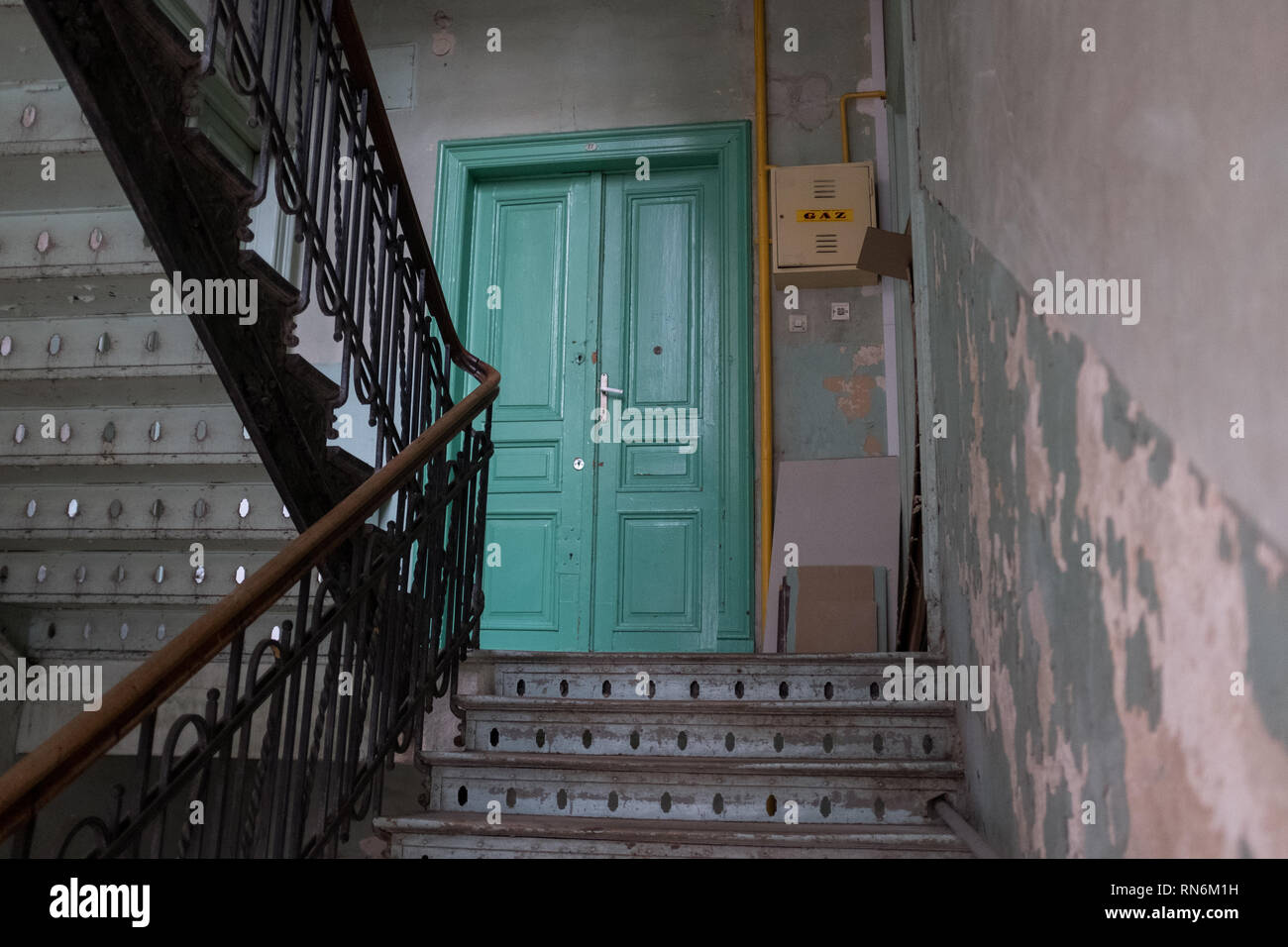 Period wooden staircase for an apartment block leading to a green door - Stock Image