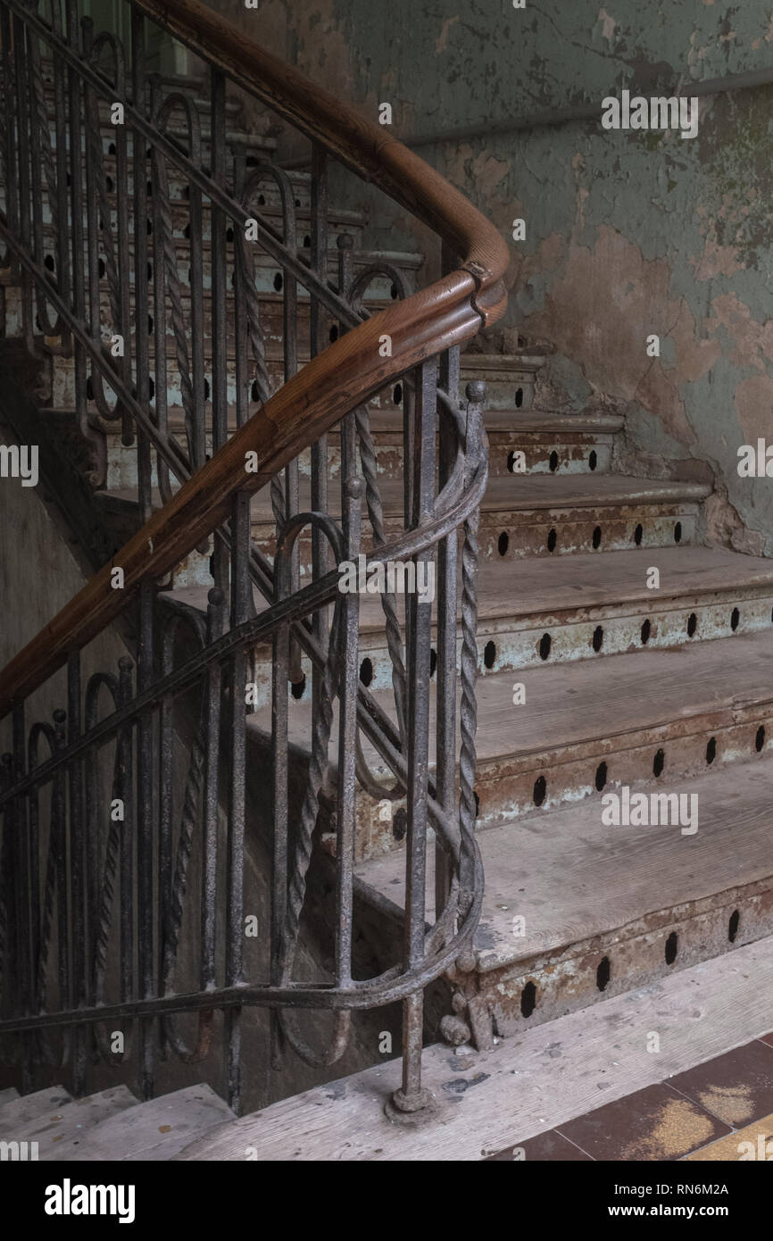 curve of a wooden staircase in a tenement block which is very tatty and old Stock Photo