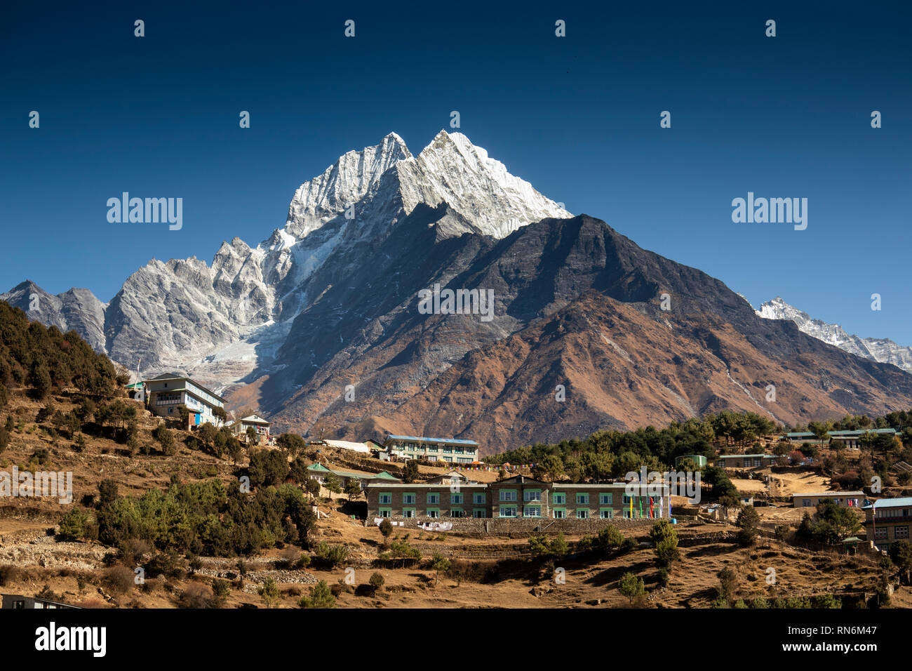 Nepal, Namche Bazaar, snow capped Thamserkhu peak above hilltop houses, Yeti Mountain Home and Hill Top Lodge and Restaurant - Stock Image