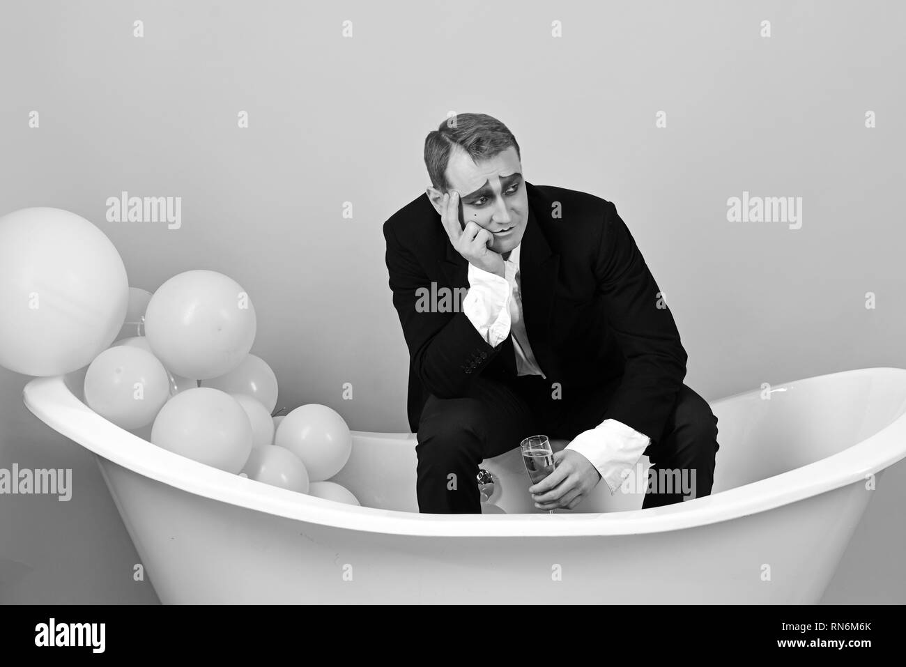 Think celebration, think champagne. Mime actor has celebration party. Mime man celebrate with champagne in bath. Comedian actor enjoy theatre party - Stock Image