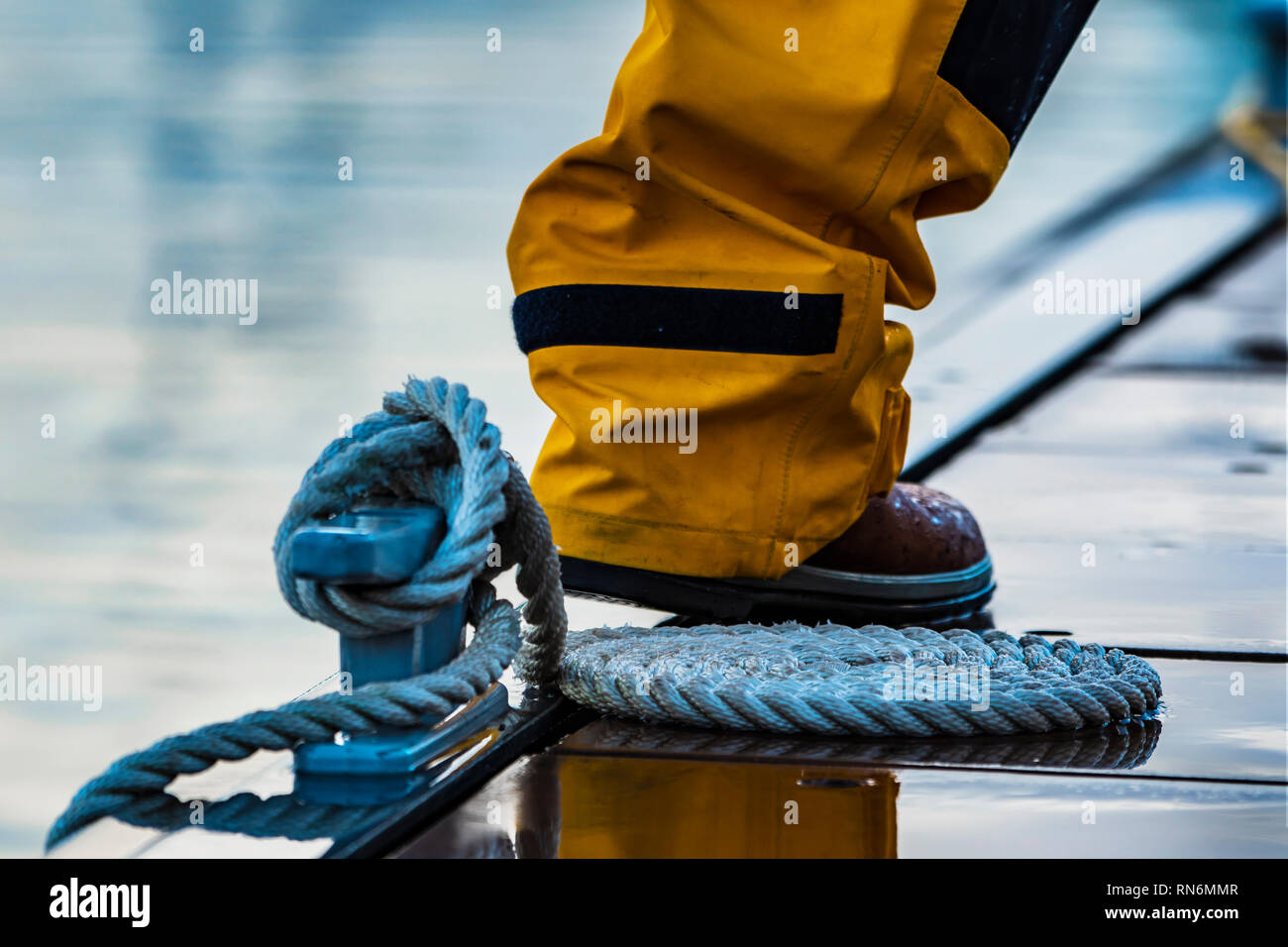 Coiled mooring line tied around cleat on a pontoon at rainy evening. - Stock Image