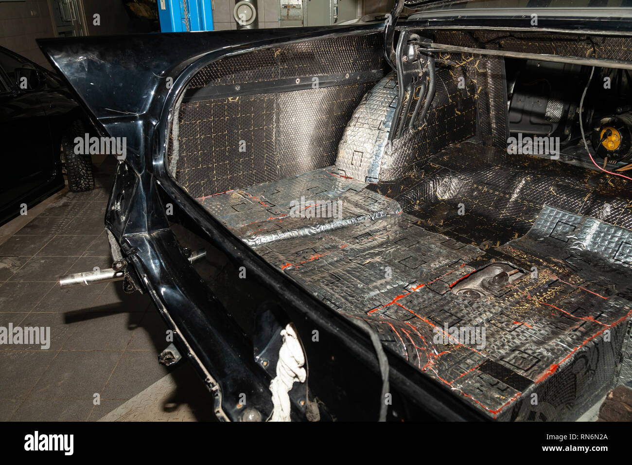 Tuning the car in a sedan body with three layers of noise insulation of the trunk. Audio and vibration isolation. Soft material. Dismantled car. Addit - Stock Image