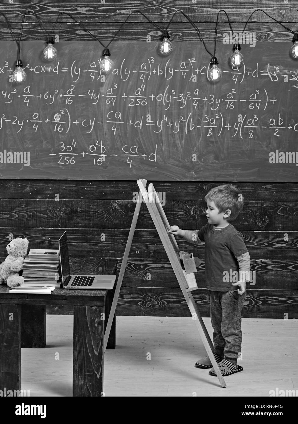 Little boy writing on chalkboard. Side view kid in front of green board with math equation. Smart little fellow studying math - Stock Image