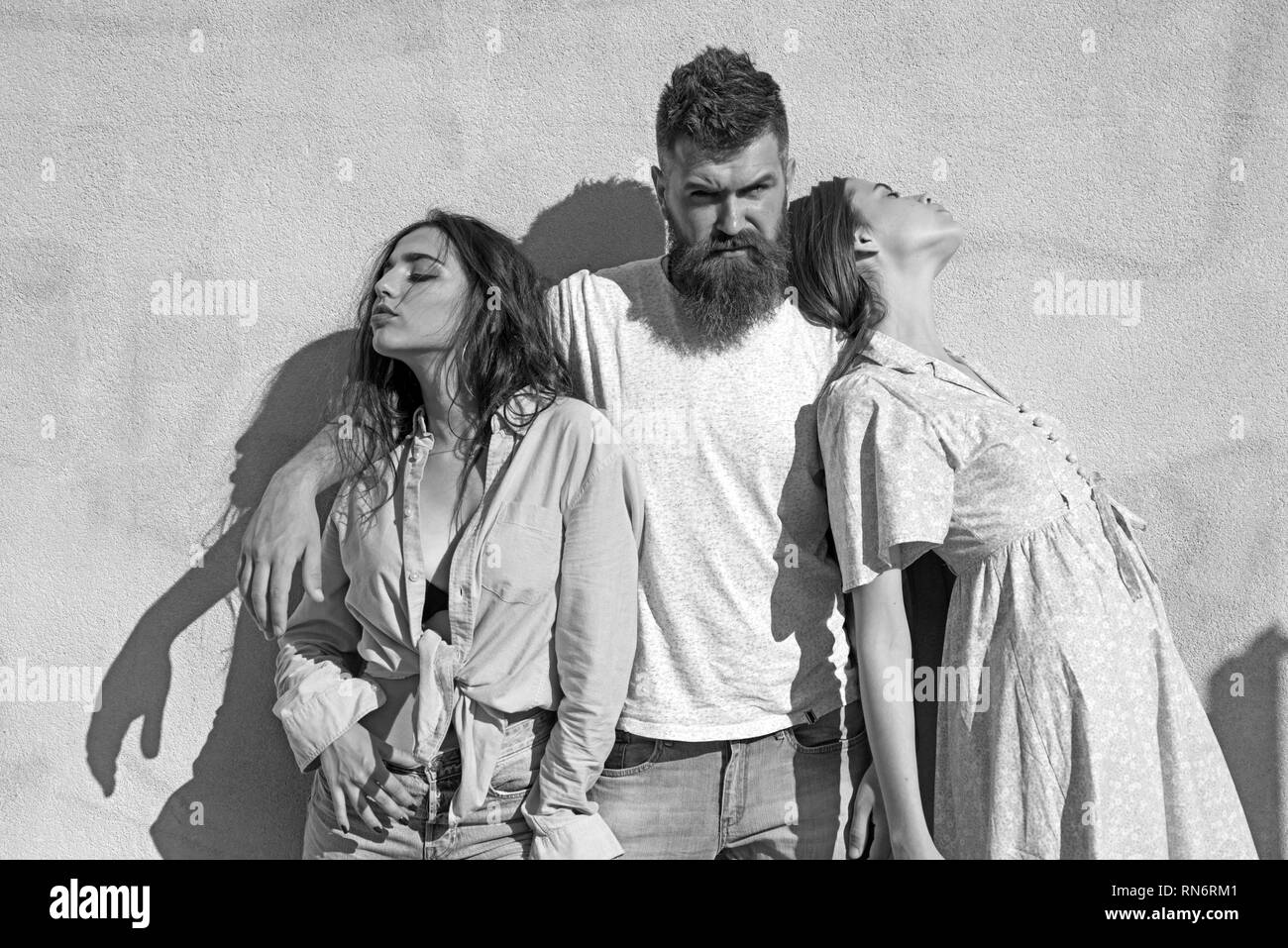 Man with beard hugs two ladies on hot sunny day. Girls turned to opposite sides while man hugs them. Love triangle concept. Threesome suffers of heat - Stock Image
