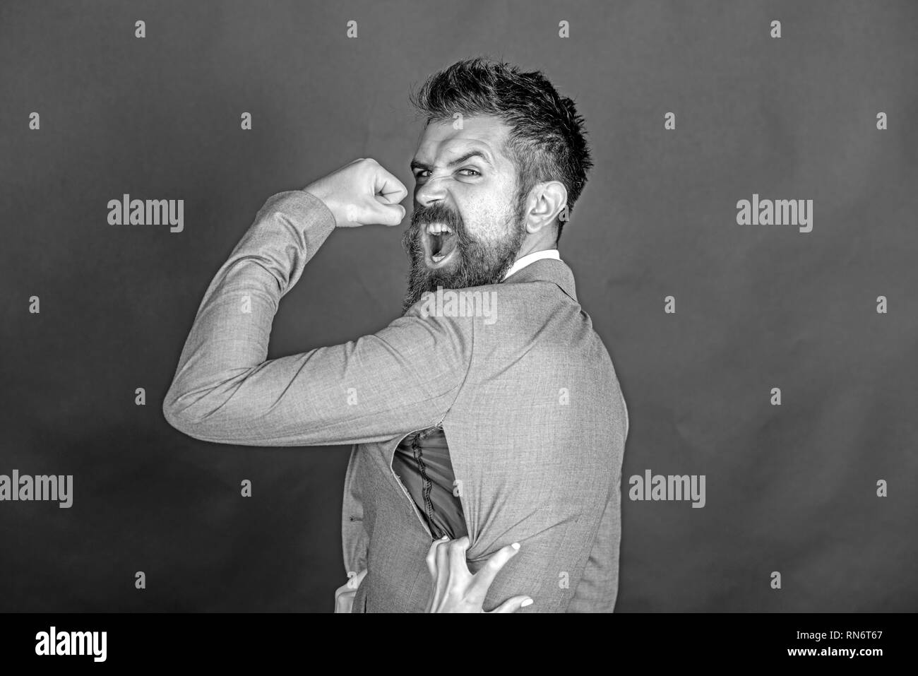 Angry guy bought counterfeit or fake brand. Man with beard wears jacket with hole on dark background. Hipster chose small size jacket, seam torn with - Stock Image