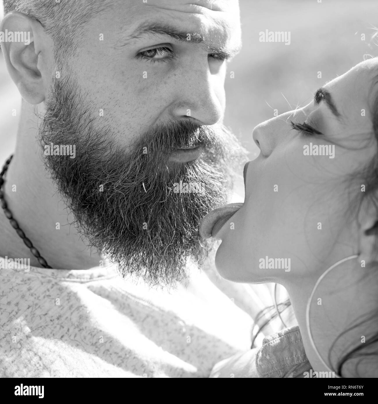 Lady with pink tongue licking bearded macho. Kiss concept. Couple kissing outdoors, nature on background, close up. Couple in love on happy faces - Stock Image