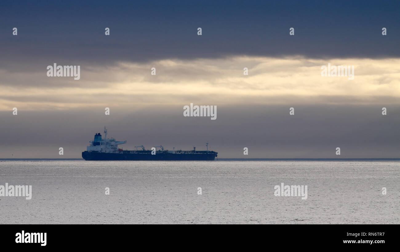 Commercial ship anchored off the coast - Stock Image